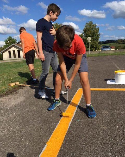 Des travaux de peinture sur le terrain de sport extérieur